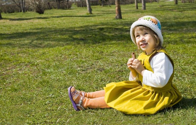 A menina senta-se em uma grama imagem de stock royalty free
