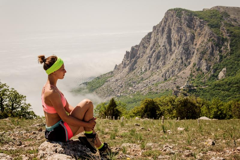 A menina senta-se em uma pedra no fundo do mar e das montanhas fotografia de stock