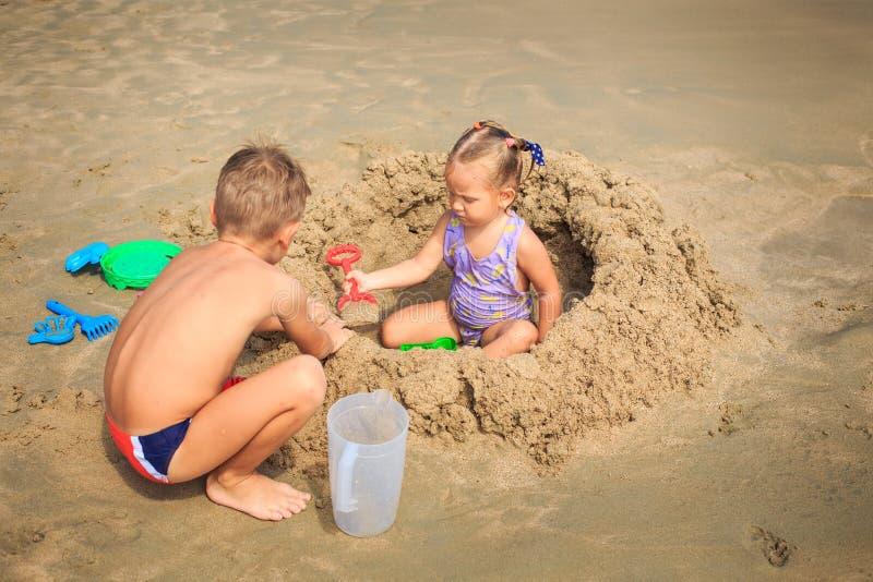 A menina senta-se entre ocupas do menino do montão da areia pelo jogo na praia imagem de stock