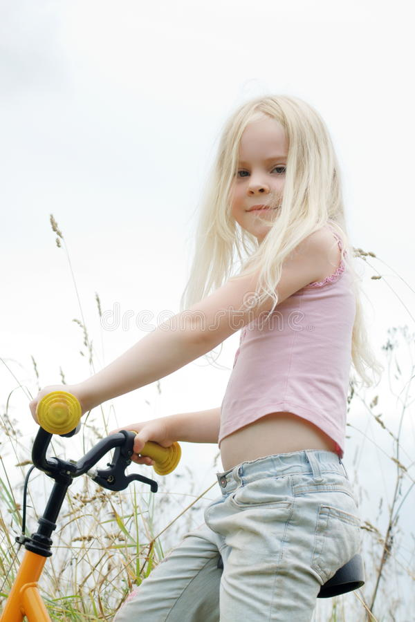 A menina senta-se na bicicleta foto de stock royalty free
