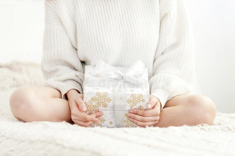 A menina senta-se na cama e em guardar um presente imagem de stock royalty free