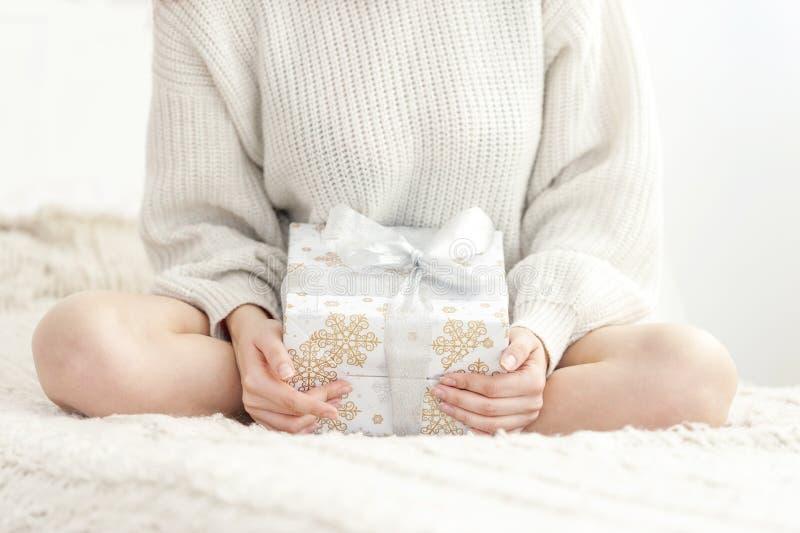 A menina senta-se na cama e em guardar um presente fotografia de stock