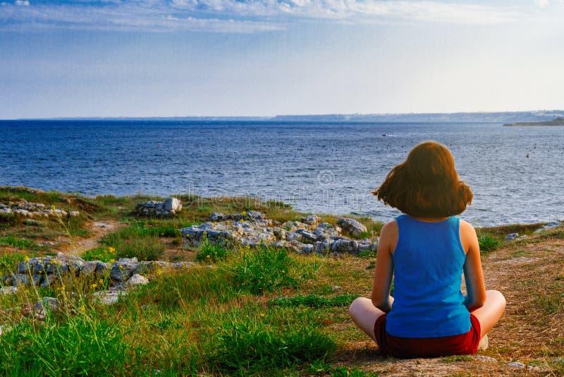 A menina senta-se na costa e olha-se o mar fotografia de stock royalty free