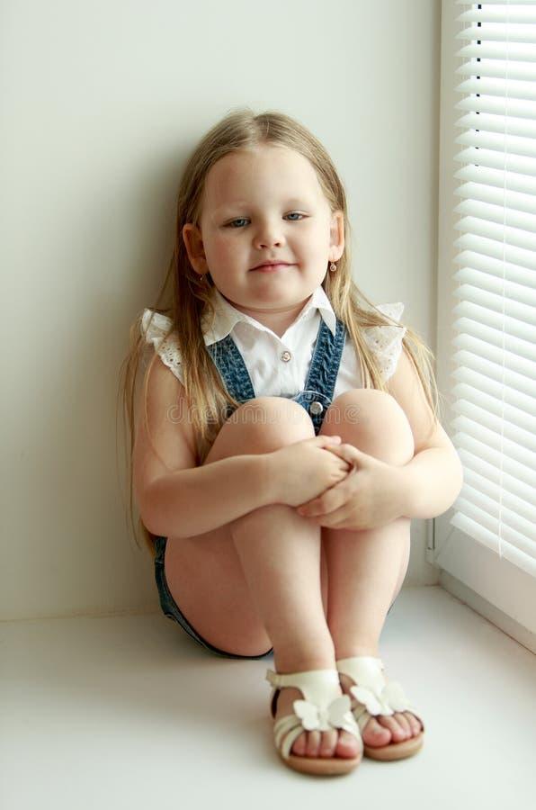 A menina senta-se na janela imagens de stock