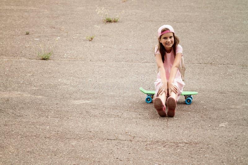 A menina senta-se na placa do patim fotografia de stock