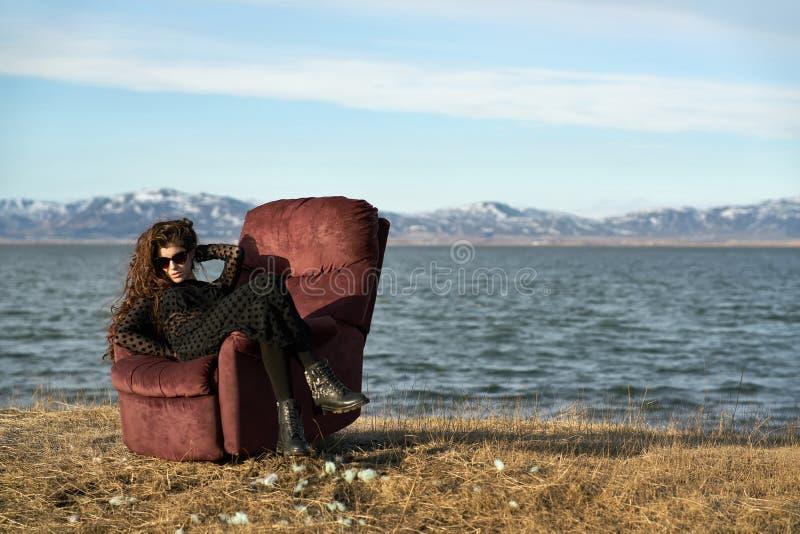 A menina senta-se na poltrona fora fotos de stock royalty free