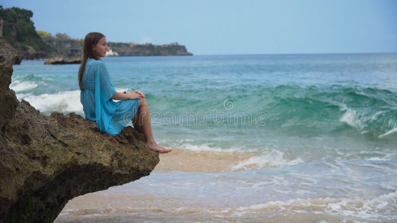 A menina senta-se na rocha e olha-se o mar Bali, Indonésia imagem de stock