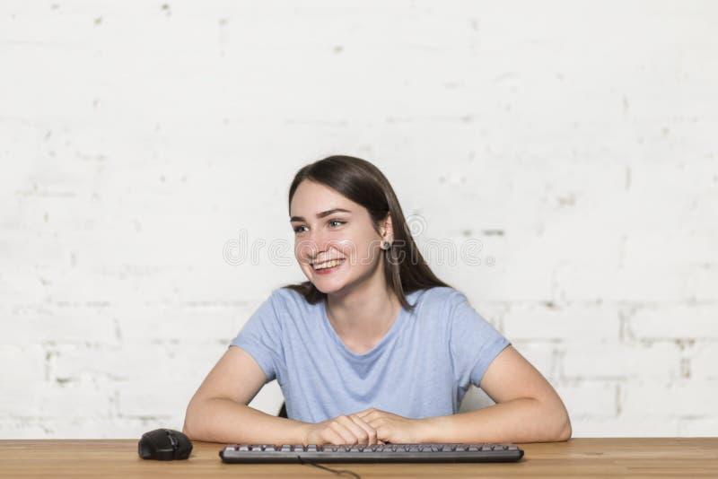 A menina senta-se na tabela e nos sorrisos Ao lado dele há um teclado e um rato fotos de stock