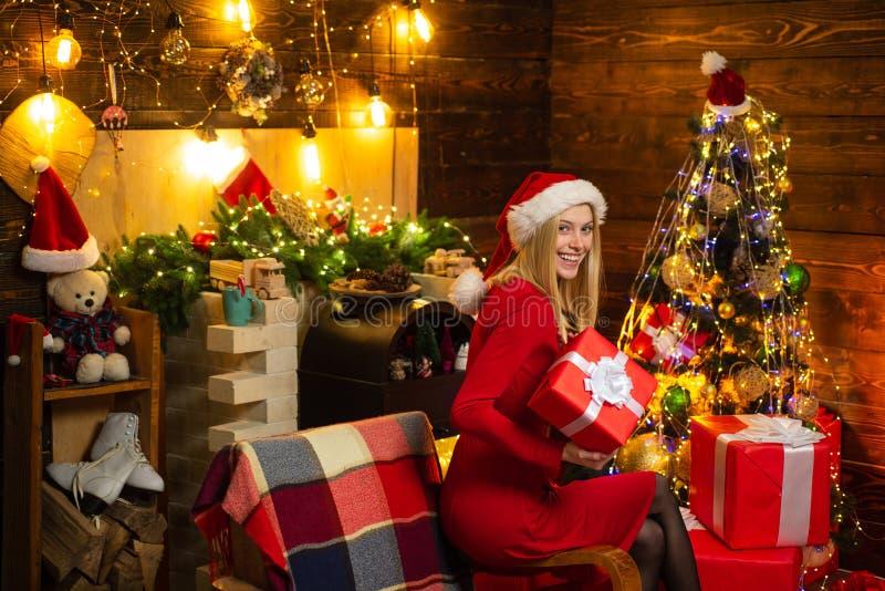 A menina senta-se perto da árvore, dos presentes e da chaminé de Natal na roupa da casa Modo do Natal Modo do ano novo Mulher atr imagem de stock