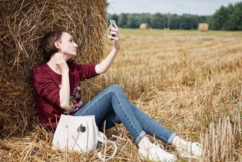 A menina senta-se perto de um monte de feno e pinta-se seus bordos com batom imagens de stock