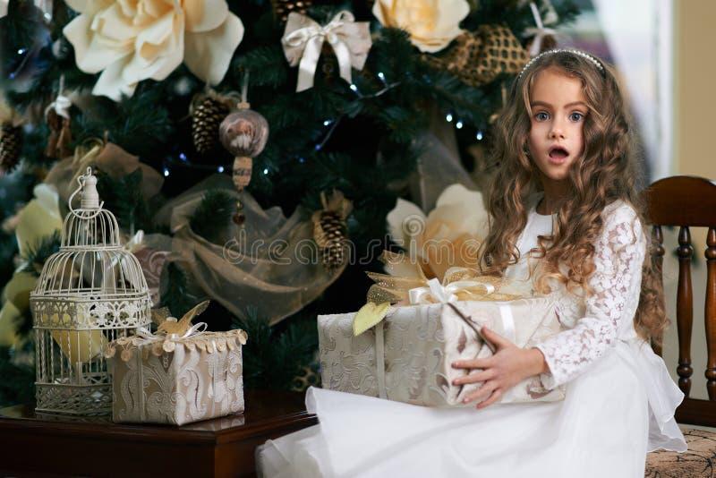 A menina senta-se perto de uma árvore de Natal com presente fotos de stock