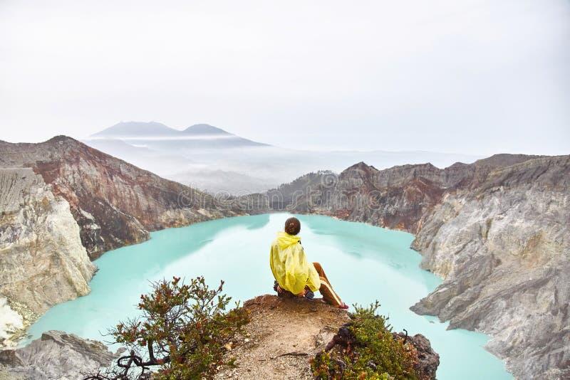 A menina senta-se sobre o vulcão e os olhares no lago na cratera imagem de stock royalty free