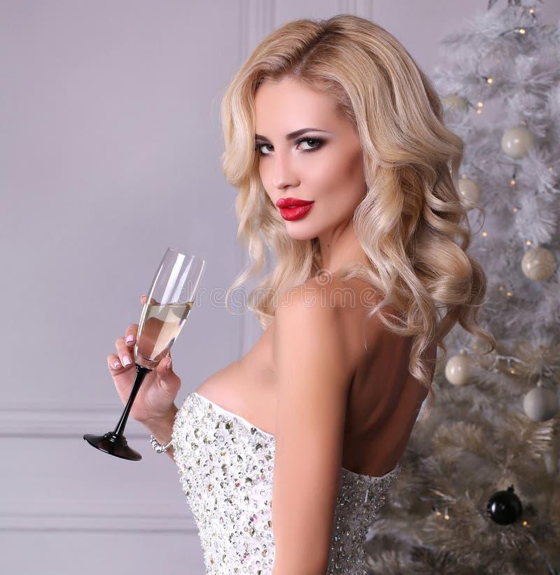 A menina 'sexy' bonita com cabelo louro veste o vestido luxuoso, holdin foto de stock
