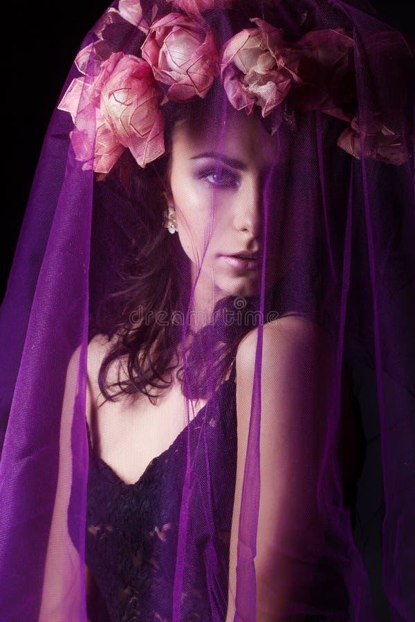 Menina 'sexy' bonita com cabelo preto em um vestido preto do laço com uma grinalda em sua cabeça coberta com um véu violeta no es fotografia de stock royalty free