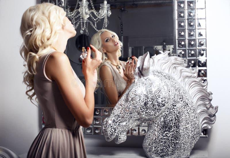 Menina 'sexy' bonita com o perfume que olha o espelho imagem de stock royalty free