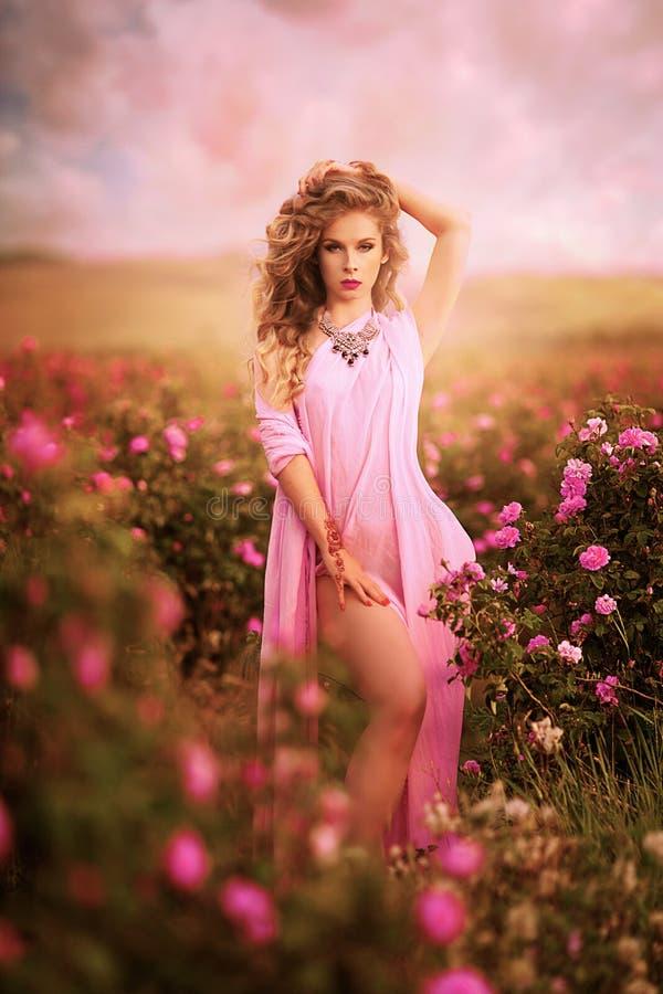 Menina 'sexy' bonita em um vestido cor-de-rosa que está nas rosas do jardim fotografia de stock