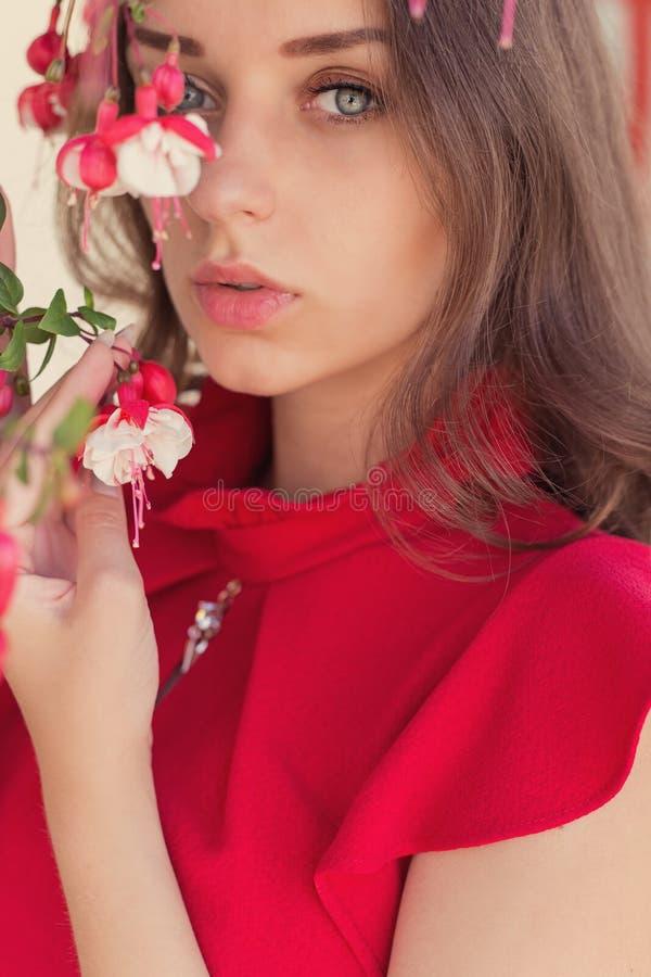 Menina 'sexy' bonita em um vestido vermelho com um olhar delicado que está cores próximas fotografia de stock