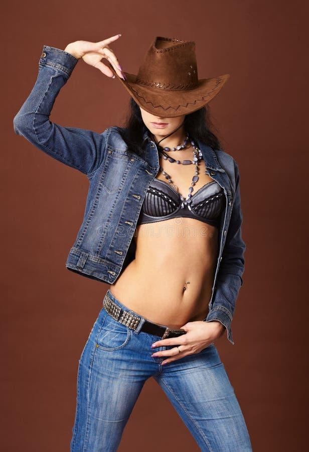Menina 'sexy' bonita nas calças de brim e no chapéu de cowboy imagem de stock