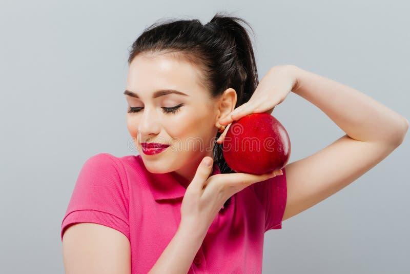 Menina 'sexy' bonita nova com o cabelo encaracolado escuro, os ombros desencapados e o pescoço, guardando a maçã vermelha grande  fotos de stock royalty free