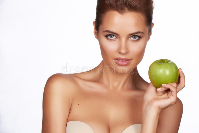 A menina 'sexy' bonita nova com o cabelo escuro, os ombros desencapados e o pescoço, guardando a maçã verde grande para apreciar  imagens de stock royalty free