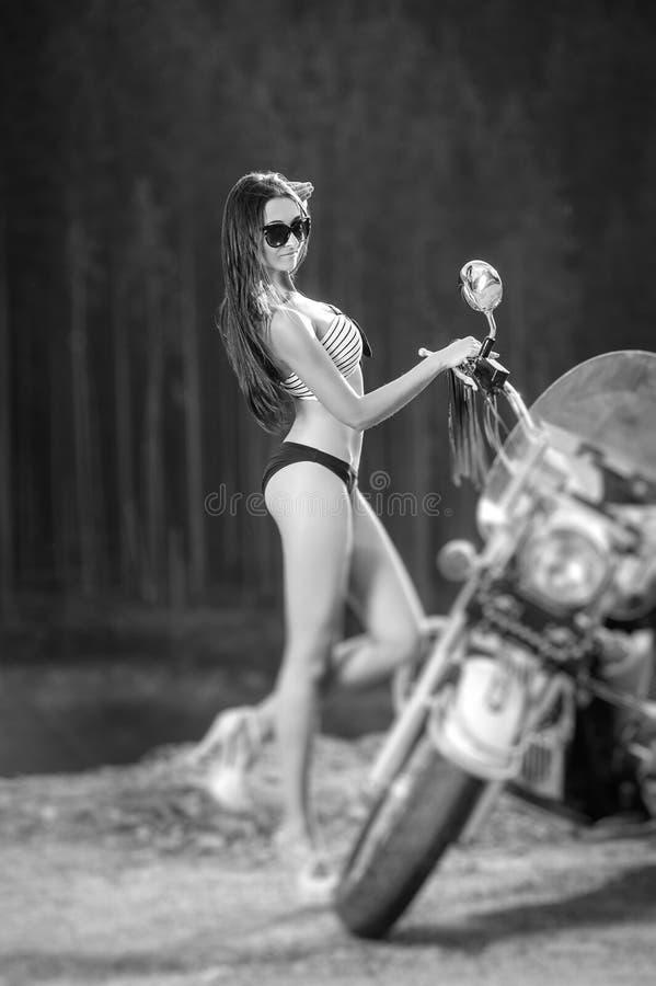 Menina 'sexy' bonita nova que está pela motocicleta imagens de stock royalty free