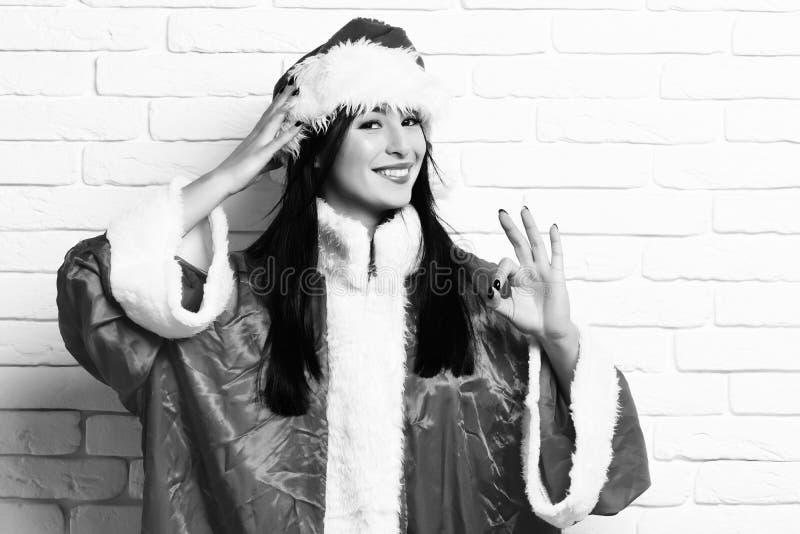 Menina 'sexy' bonito bonita de Santa ou mulher moreno de sorriso na camiseta vermelha com o chapéu do Natal ou do xmas e mostrar  fotos de stock royalty free