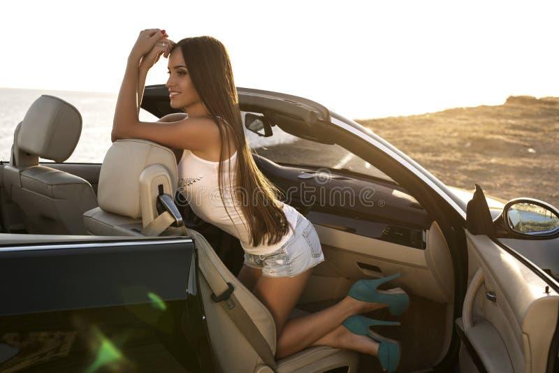 Menina 'sexy' com o cabelo escuro que levanta no cabriolet luxuoso imagem de stock