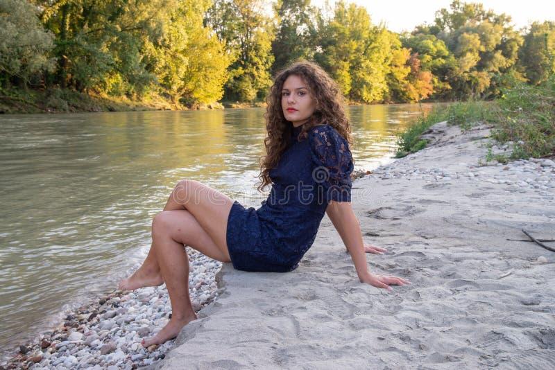 Menina 'sexy' com o cabelo marrom ondulado longo que senta-se no banco de um rio fotos de stock royalty free