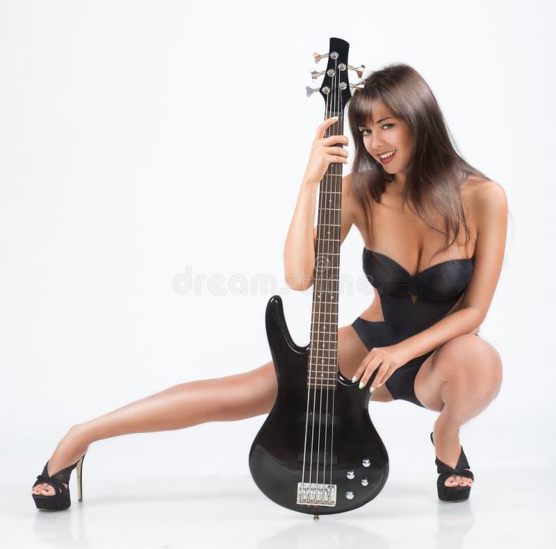Menina 'sexy' com uma guitarra. Em um roupa de banho preto, imagens de stock royalty free