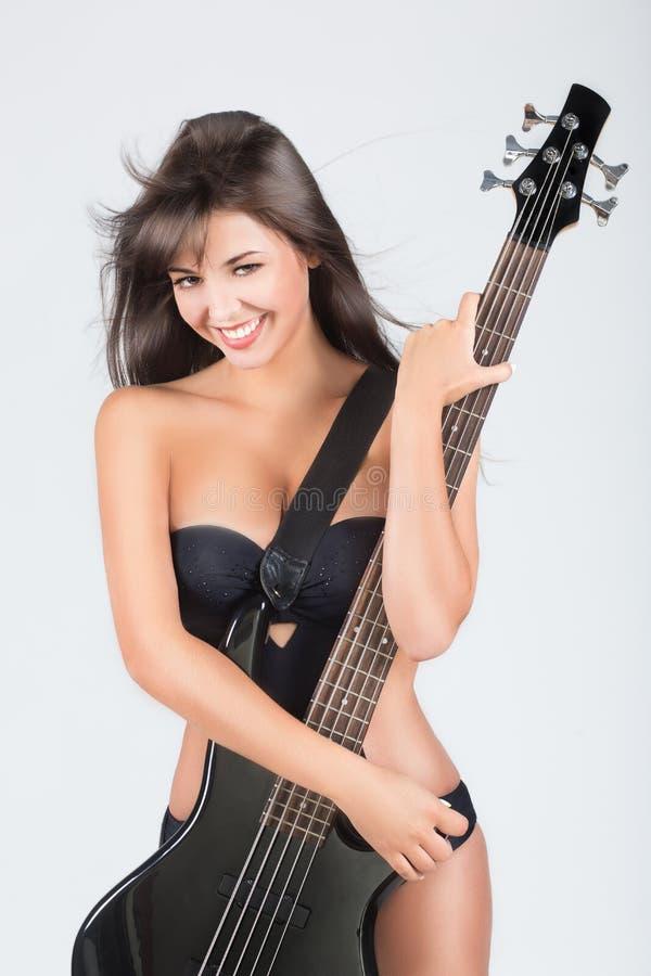 Menina 'sexy' com uma guitarra. Em um roupa de banho preto, imagem de stock
