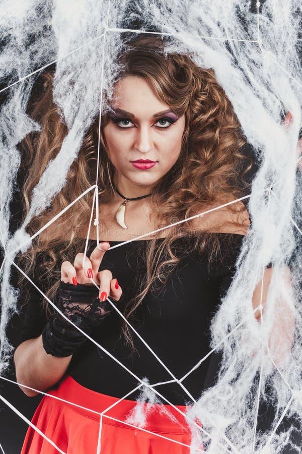 A menina 'sexy' da bruxa da beleza travou em uma Web de aranha Projeto da arte da forma A menina modelo gótico bonita com Dia das fotografia de stock