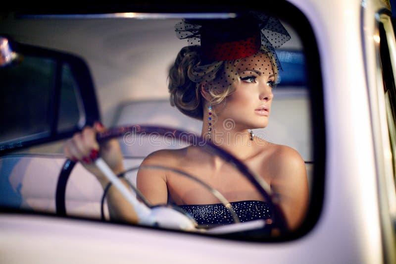 Menina 'sexy' da forma que senta-se no carro velho fotografia de stock royalty free