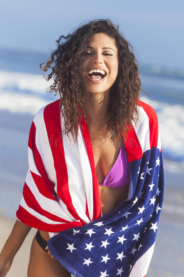 Menina 'sexy' da mulher nova na bandeira americana na praia imagem de stock