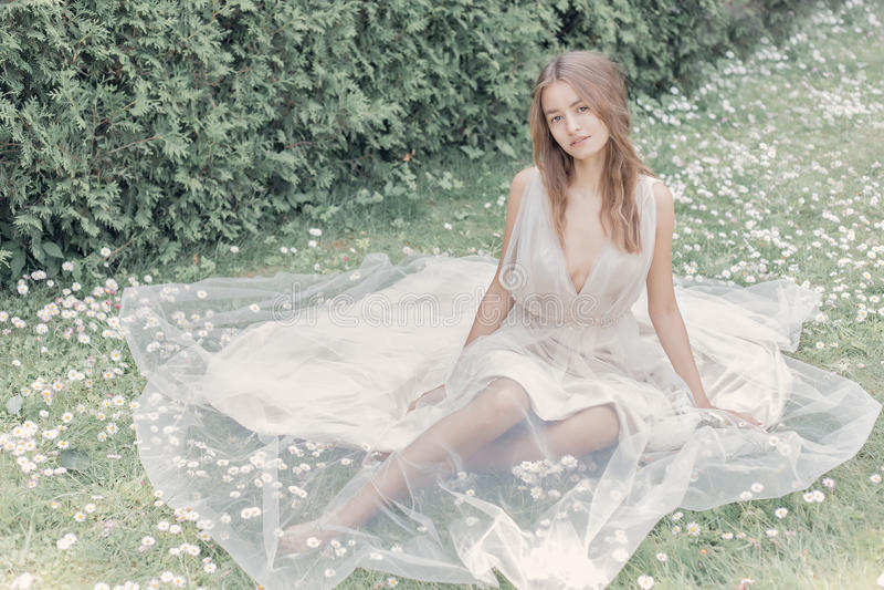 A menina 'sexy' da noiva delicada bonita em um vestido de casamento bege leve anda no dia morno ensolarado brilhante do jardim foto de stock