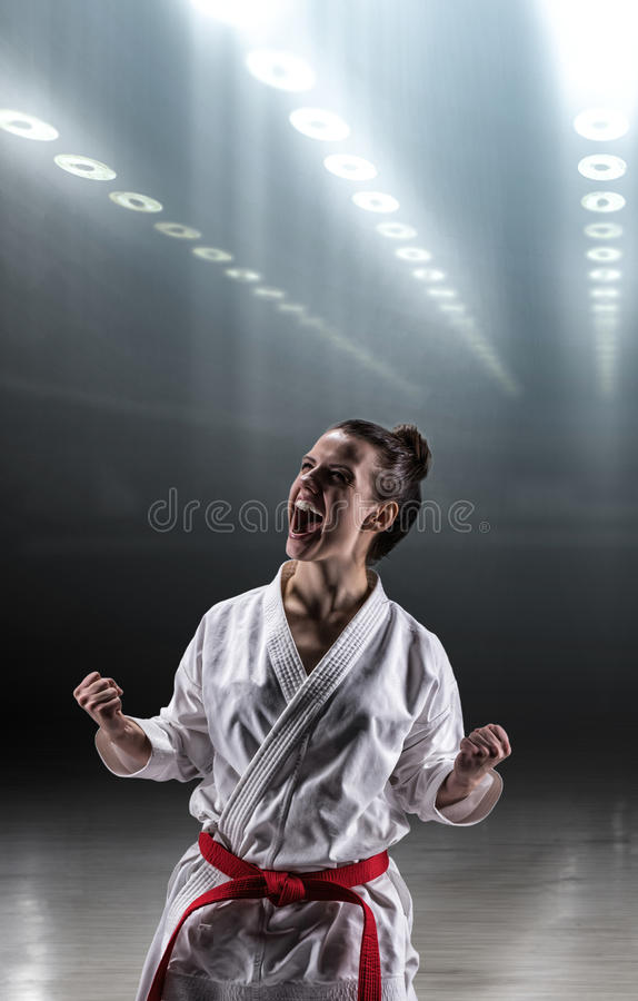 A menina 'sexy' em um karaté do quimono exulta a vitória foto de stock
