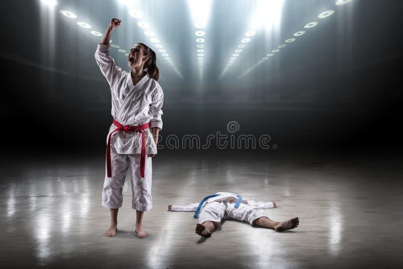 A menina 'sexy' em um karaté do quimono exulta a vitória fotografia de stock