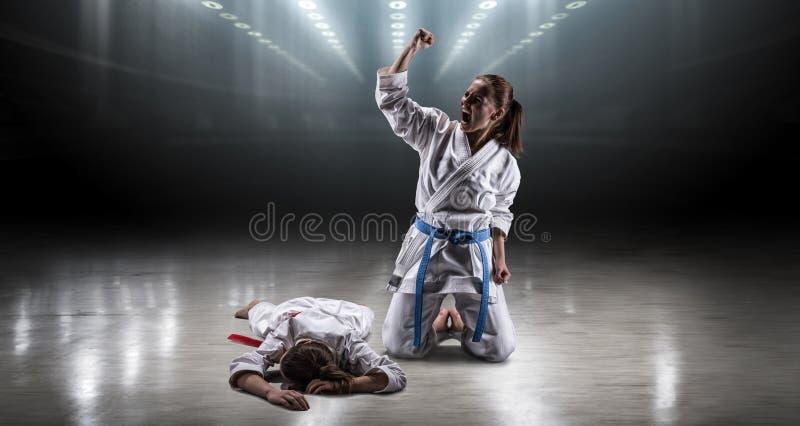 A menina 'sexy' em um karaté do quimono exulta a vitória fotografia de stock royalty free