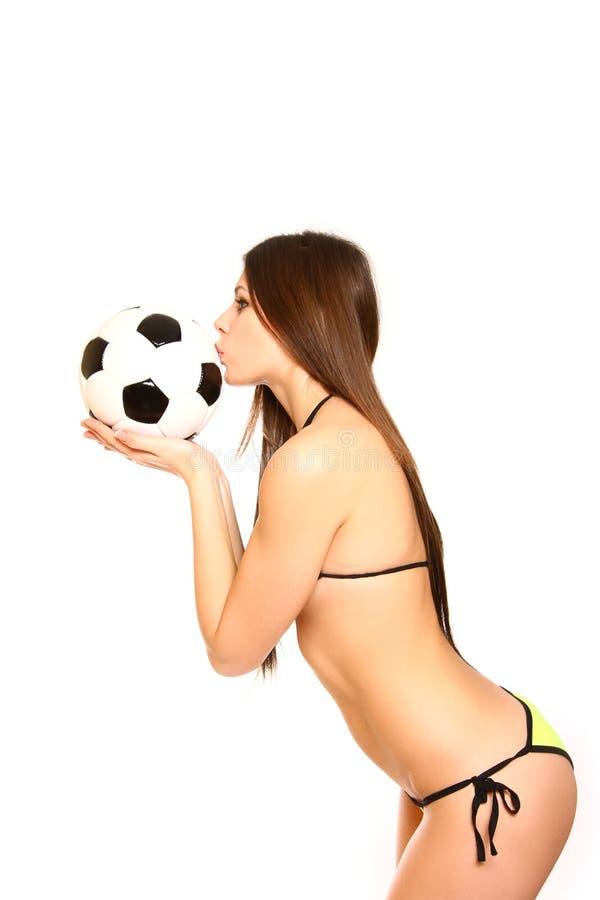 Menina 'sexy' em um roupa de banho que guardara e que beija uma bola de futebol em um w foto de stock royalty free