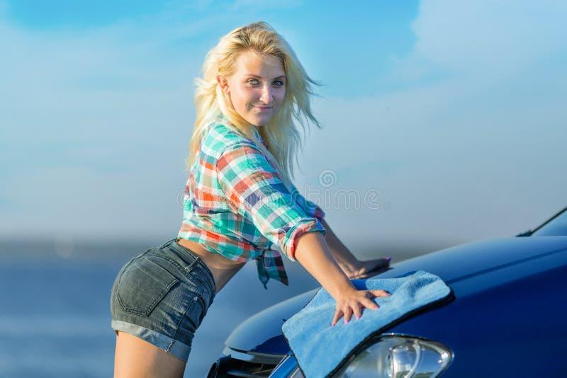 A menina 'sexy' lava a capa do carro foto de stock
