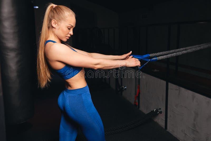 Menina 'sexy' louro bonita que executa exercícios para os braços e os Abs imagem de stock