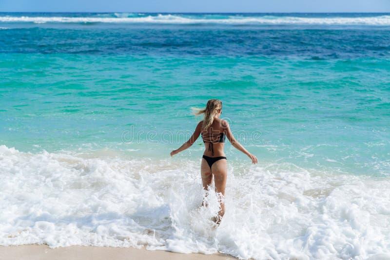 A menina 'sexy' magro no roupa de banho preto vai nadar no oceano na praia foto de stock royalty free