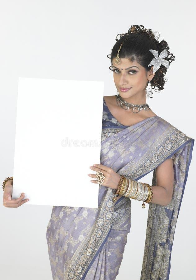 Menina 'sexy' no sari extravagante que prende a placa branca fotografia de stock royalty free