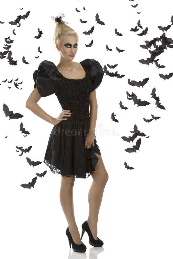 Menina 'sexy' no terno de Halloween com mão no quadril imagem de stock