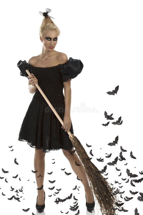 Menina 'sexy' no terno de Halloween com vassoura foto de stock