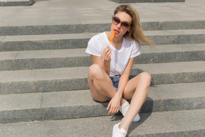 Menina 'sexy' nova bonita nos óculos de sol que come o gelado na escada e que lambe os bordos gordos um o dia quente ensolarado b foto de stock