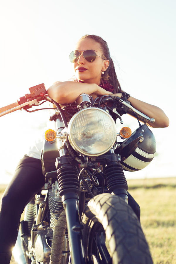 Menina 'sexy' nova que senta-se na motocicleta feita sob encomenda do vintage e no suco bebendo Retrato exterior do estilo de vid imagem de stock