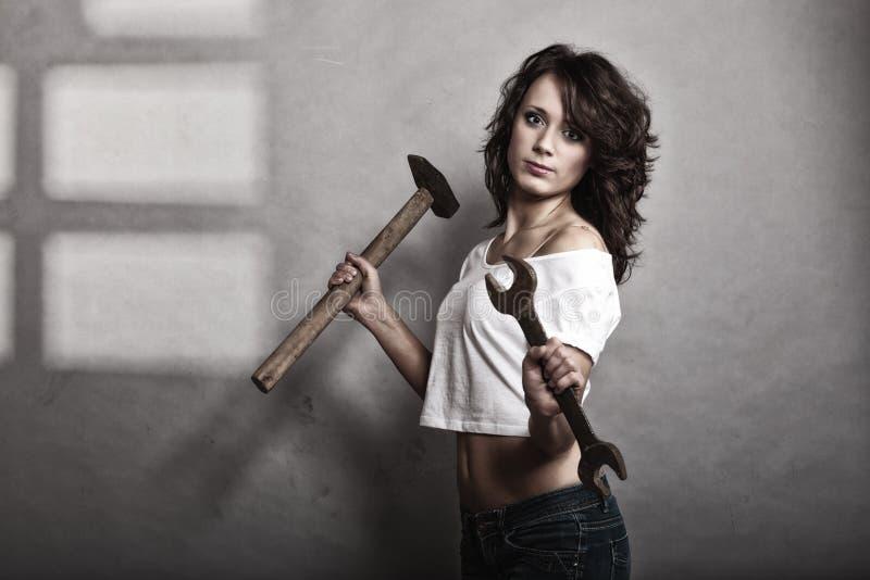 Menina 'sexy' que guarda a chave inglesa do martelo e da chave imagens de stock