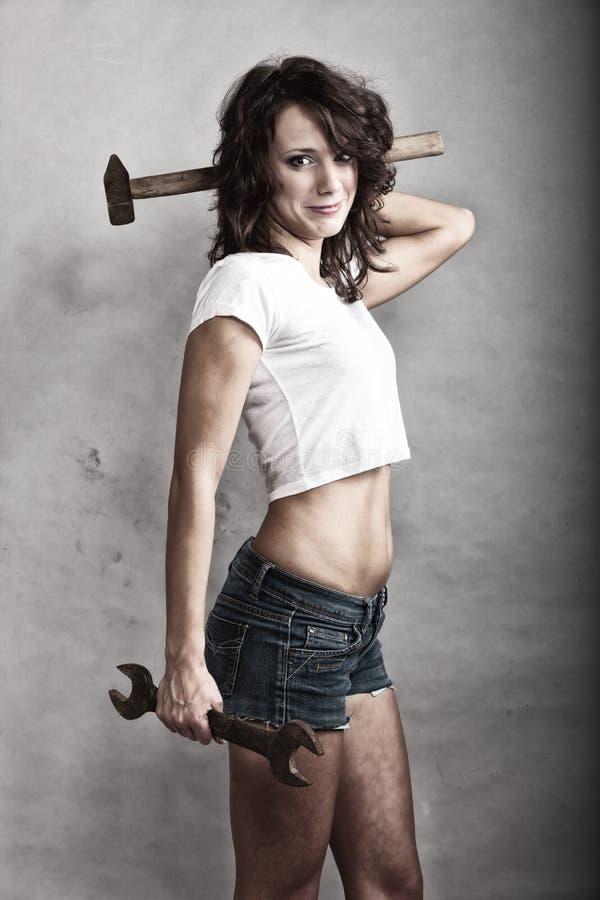 Menina 'sexy' que guarda a chave inglesa do martelo e da chave fotos de stock