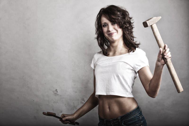 Menina 'sexy' que guarda a chave inglesa do martelo e da chave fotografia de stock