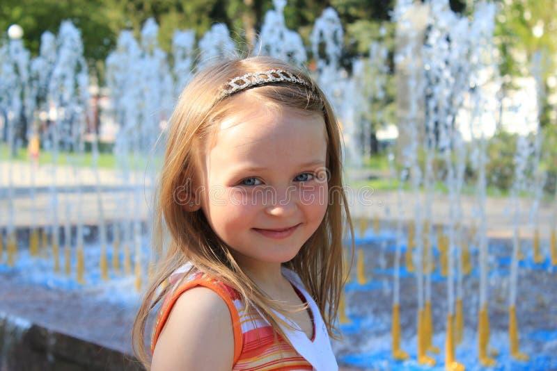 Menina simpática pequena perto das fontes fotografia de stock